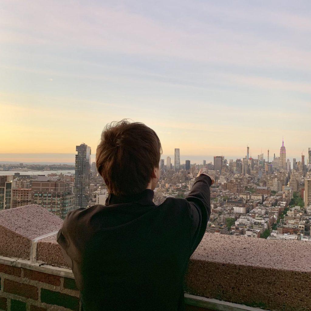 夕日を背景に紫色に輝くエンパイア・ステート・ビルを見つめ、指を指すジミン