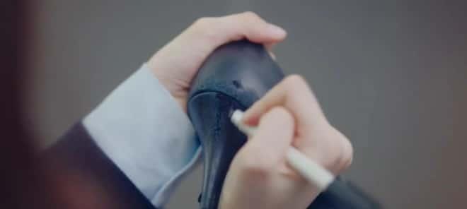 革靴の剥げてしまった部分を黒いマジックペンを塗りつぶすダルミ